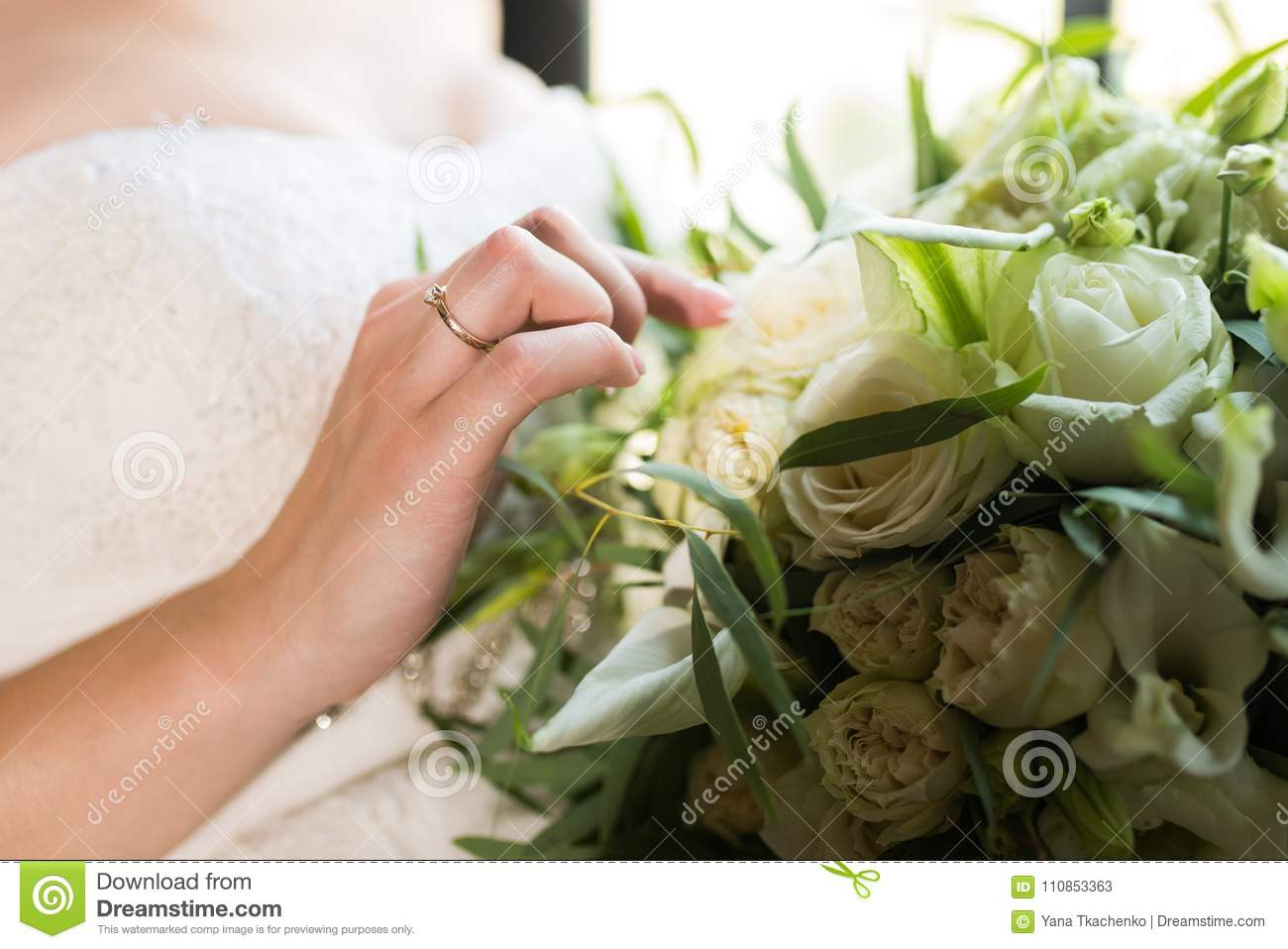 Bride Touching Wedding Bouquet With One Hand With Wedding Ring On