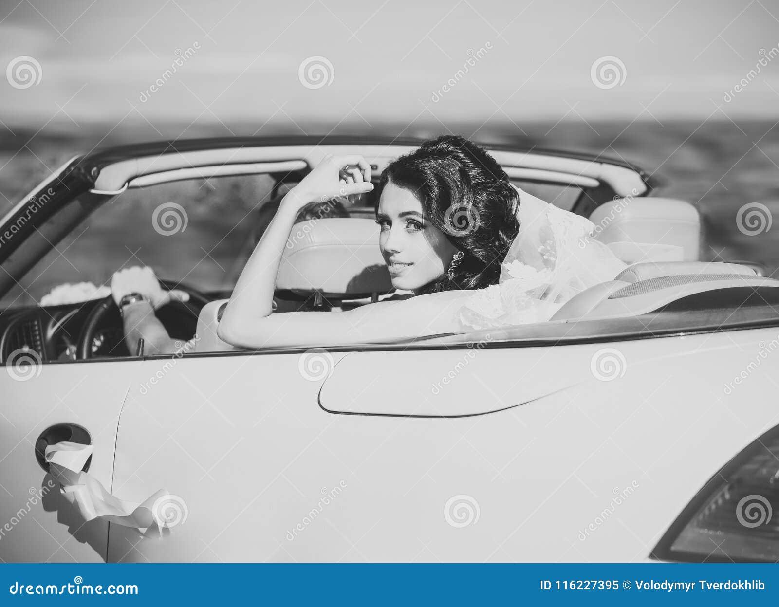 Bride in veil sit in white car cabriolet, wedding