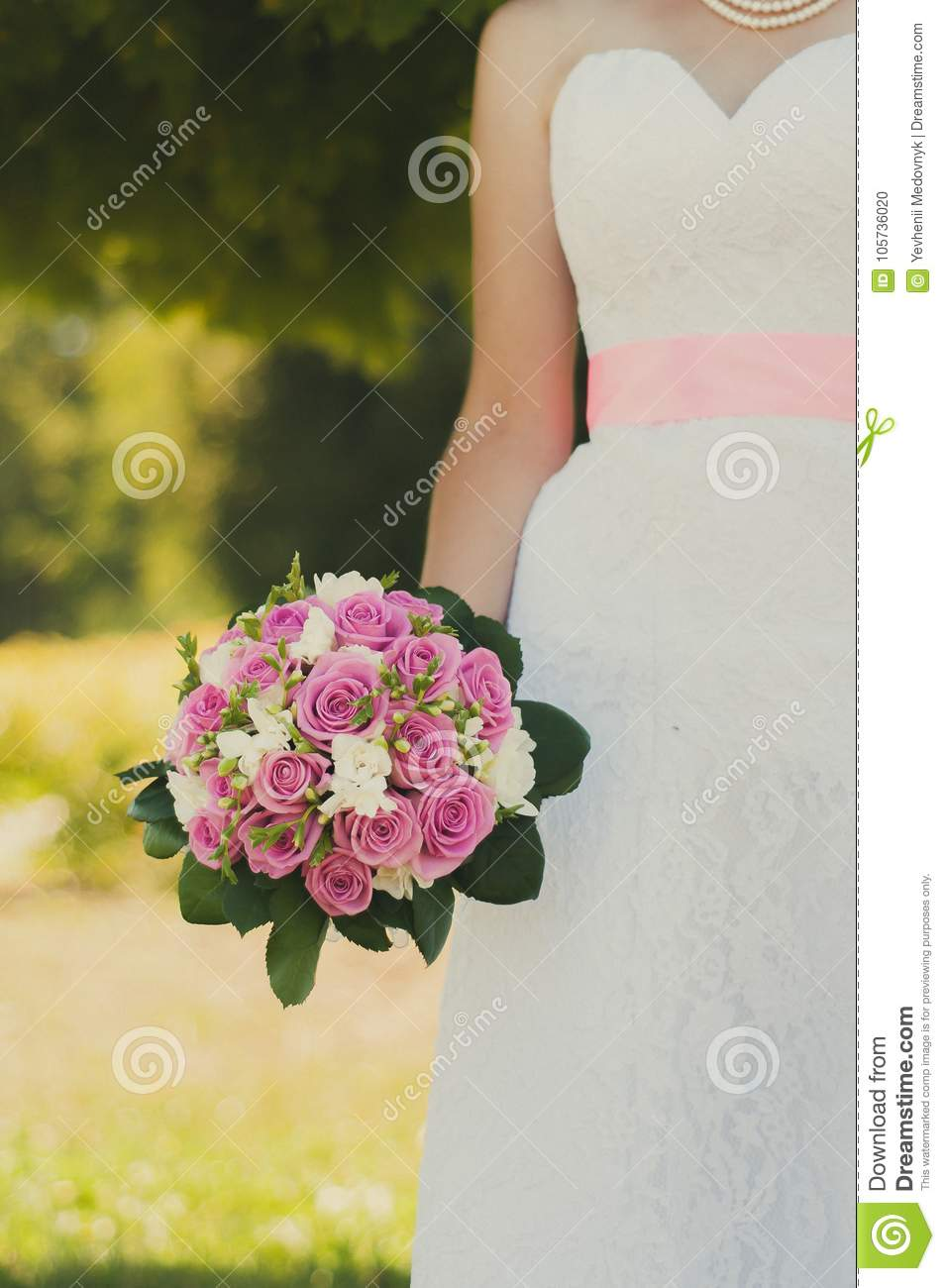 Bride after the wedding ceremony in the sun park holds a beautiful bouquet