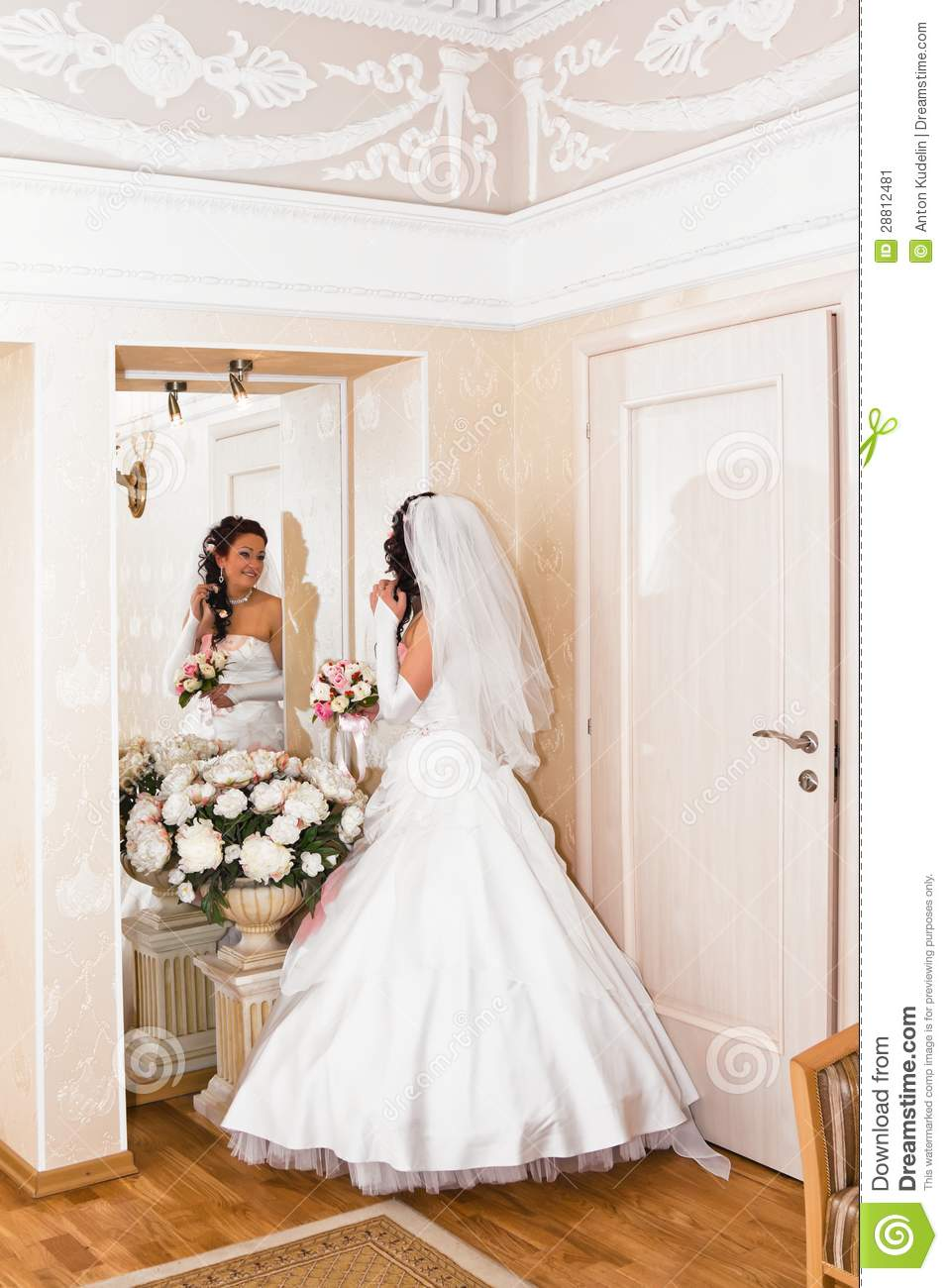 Bride In Wedding Dress Looks In The Mirror Stock Image
