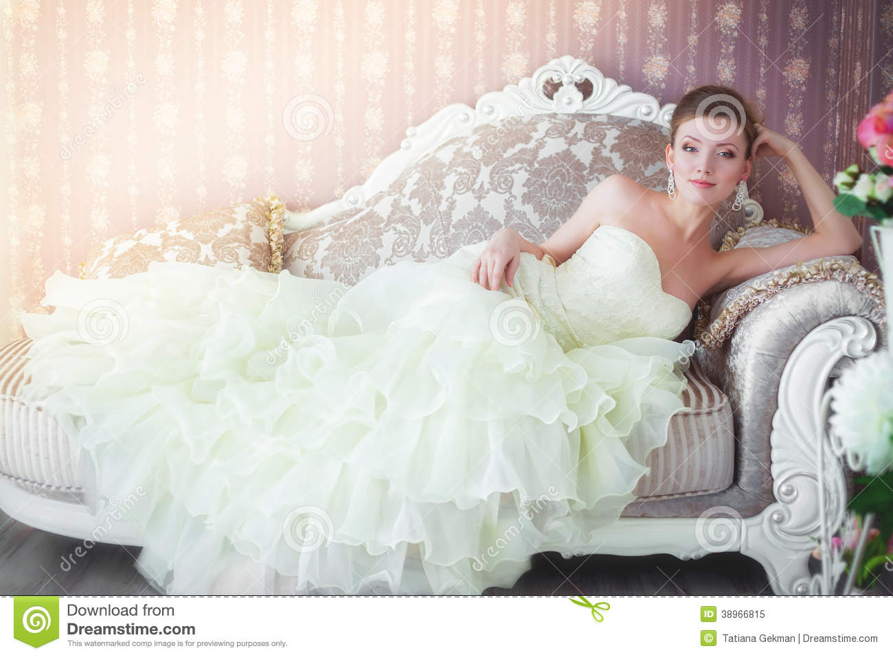 Bride In Wedding Dress Sitting On The Couch Stock Photo