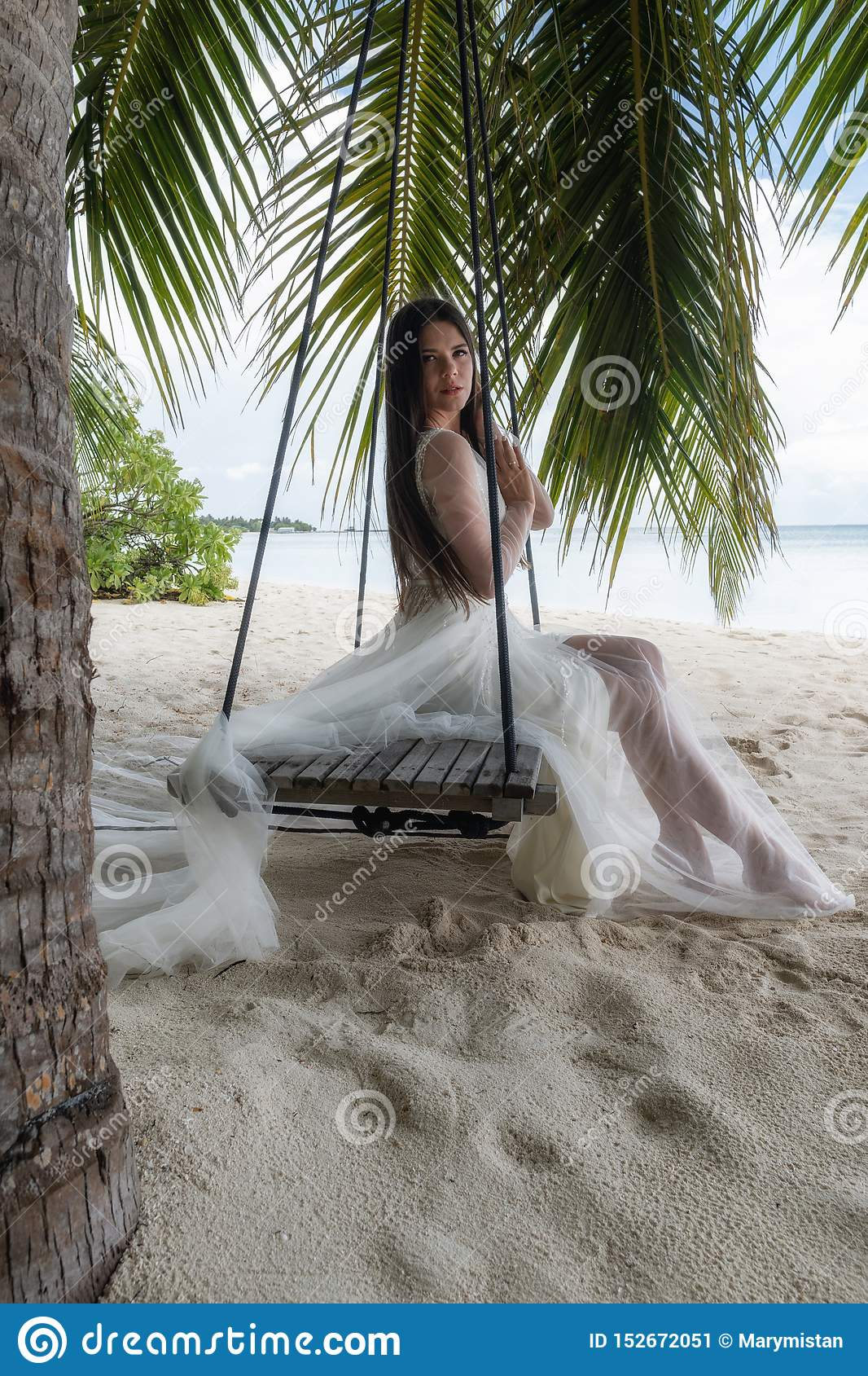 A bride in a white dress is riding on a swing under a big palm tree