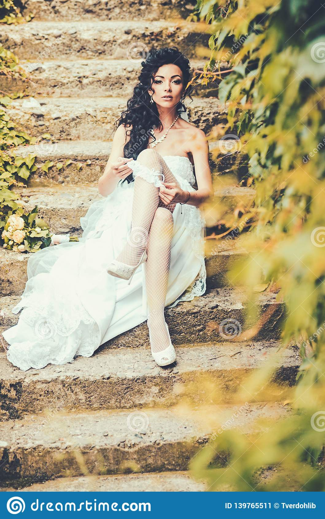 fa5f554b7 Bride in white dress sit on steps outdoor. Woman wear lace garter on leg.  woman in stockings lingerie on wedding day. Girl with bridal makeup and  hairstyle.