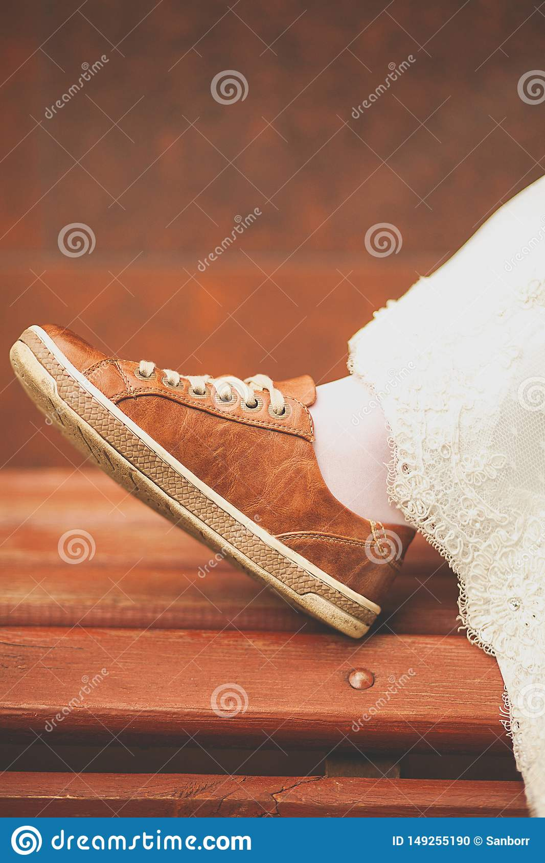 Bride in white wedding dress and brown sneakers or sports shoes. Women`s foot in a sneaker, on a wooden painted bench, close-up,
