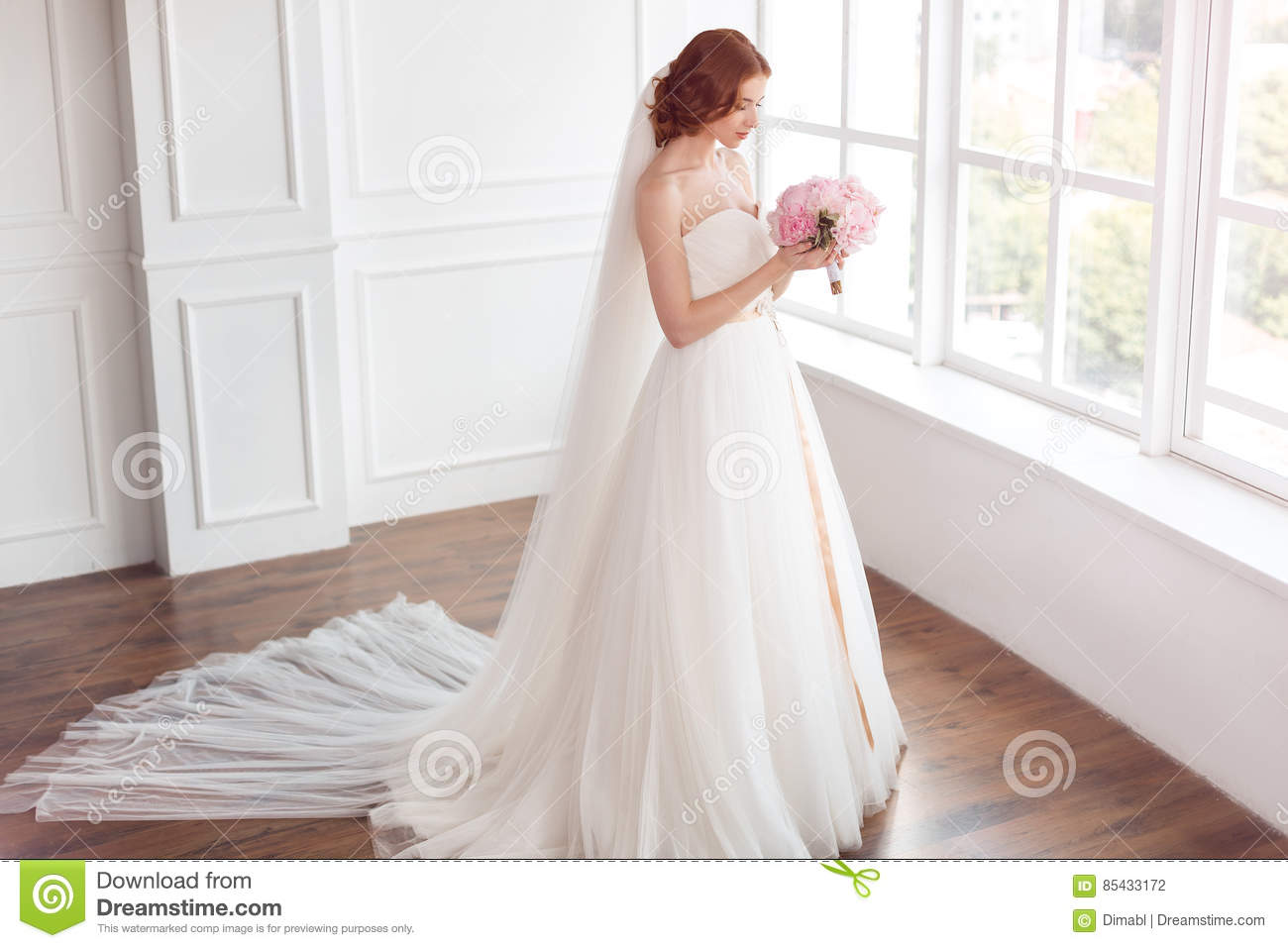 Bride in white wedding dress and long veil with bouquet of flowers