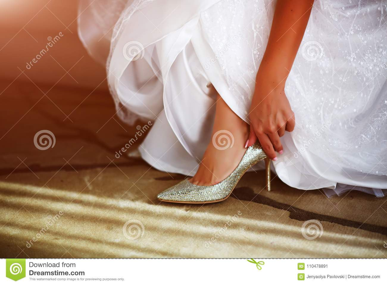 ff2ebe3a4ef3 Bride In White Wedding Dress Putting On Silver Shoes Stock Image ...