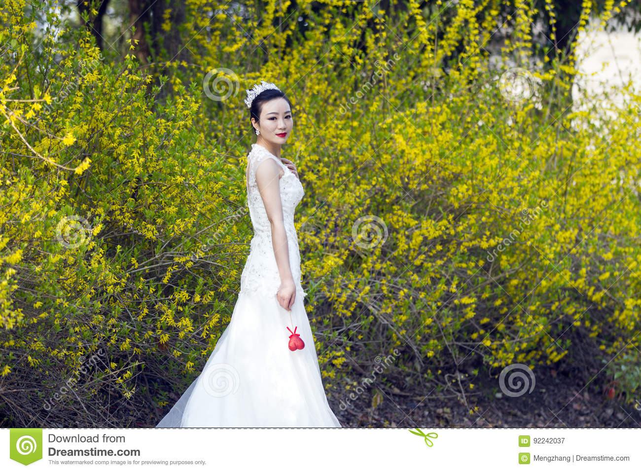 A Bride With White Wedding Dress Stand By Golden Jasmine Flowers