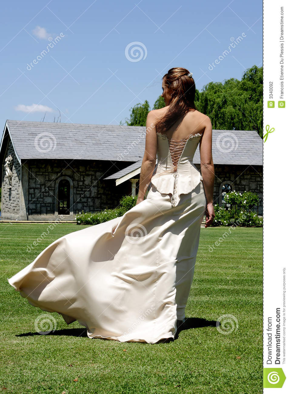 Bride walking outside and wind blowing her dress