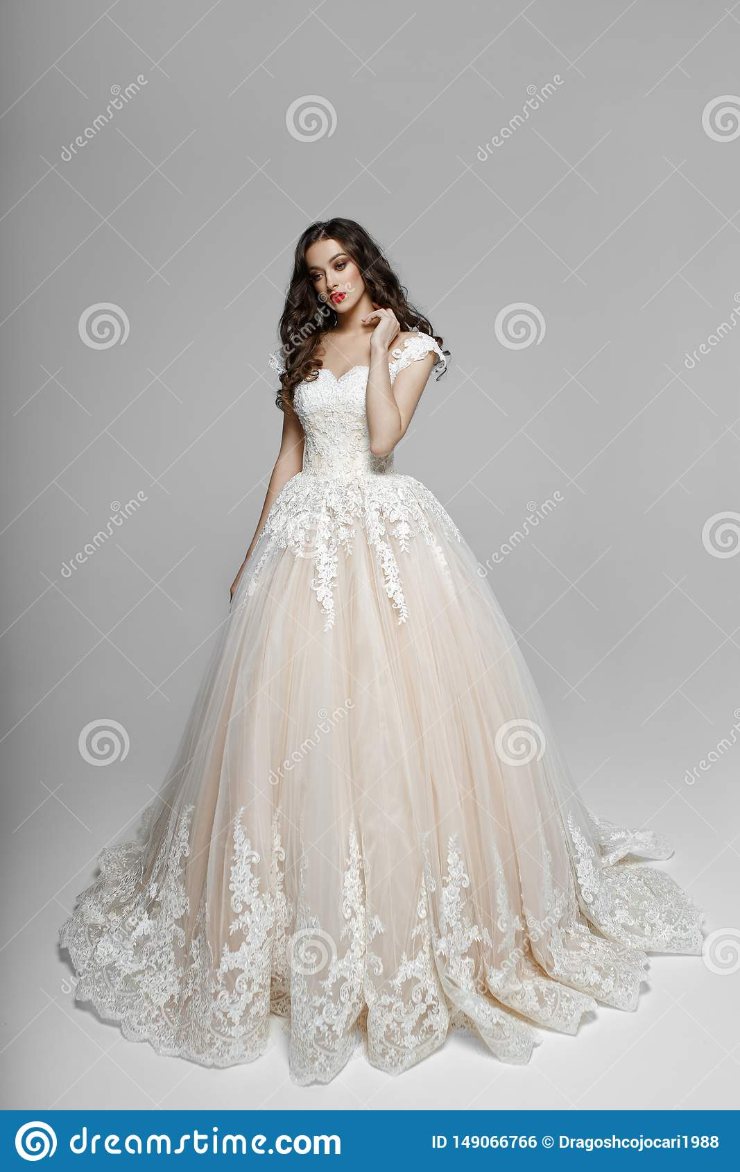 Beautiful girl with curly hair in wendding dress, he touches his neck with his hand, isolated on a white background.