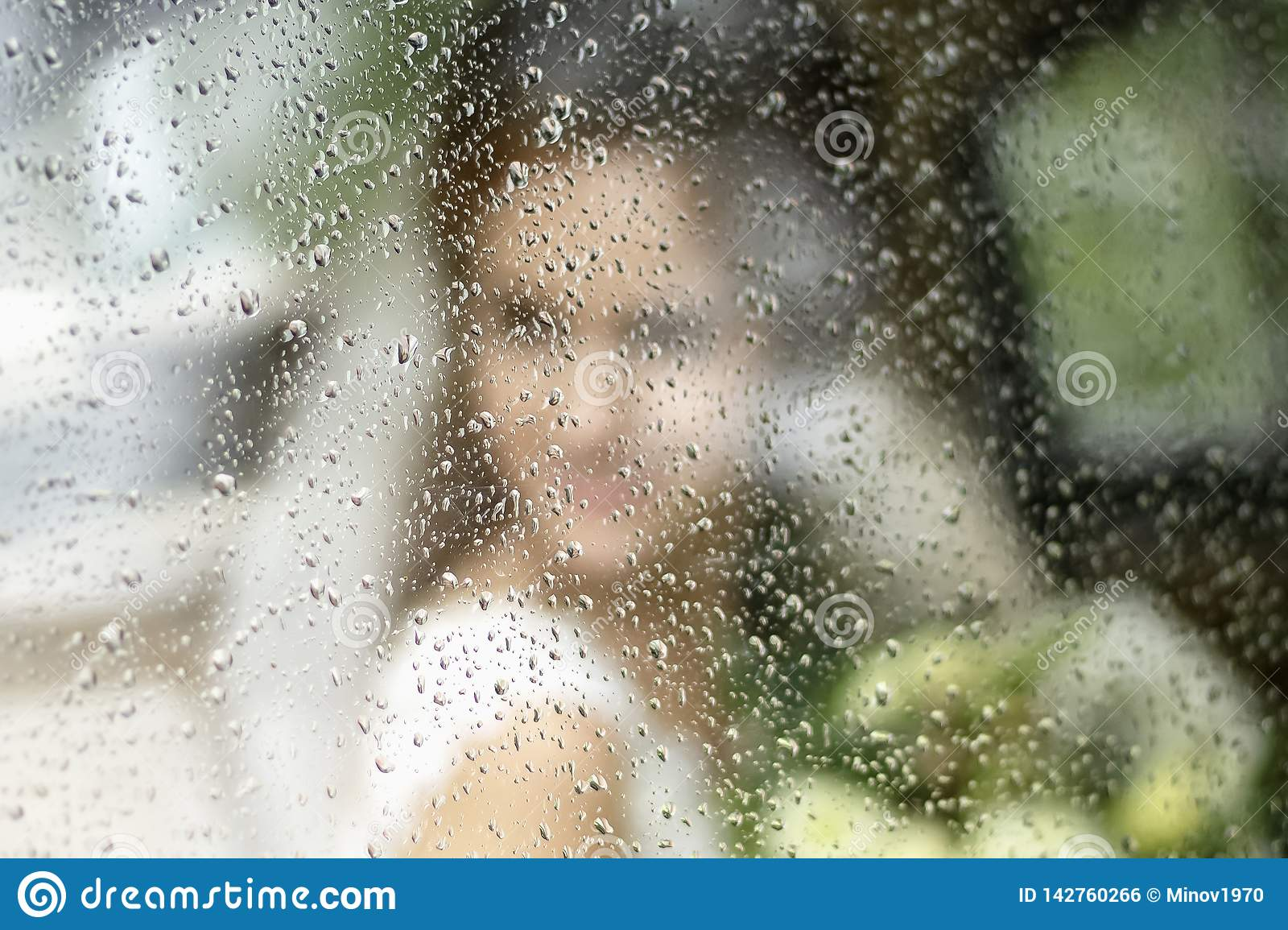 The brides silhouette in a wedding dress with a bouquet of flowers through glass in rain drops