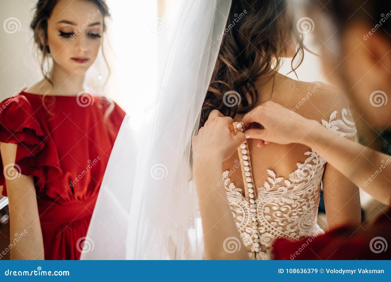 Bridesmaids помогают невесте получить готовыми для свадьбы