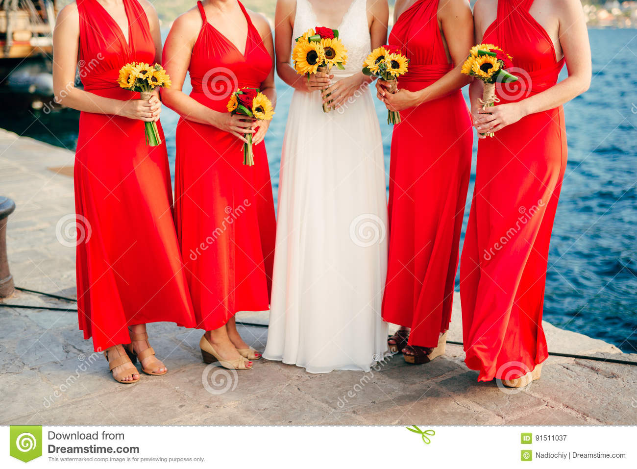 Bridesmaids in red dresses, in hands bouquets of sunflowers. Wed