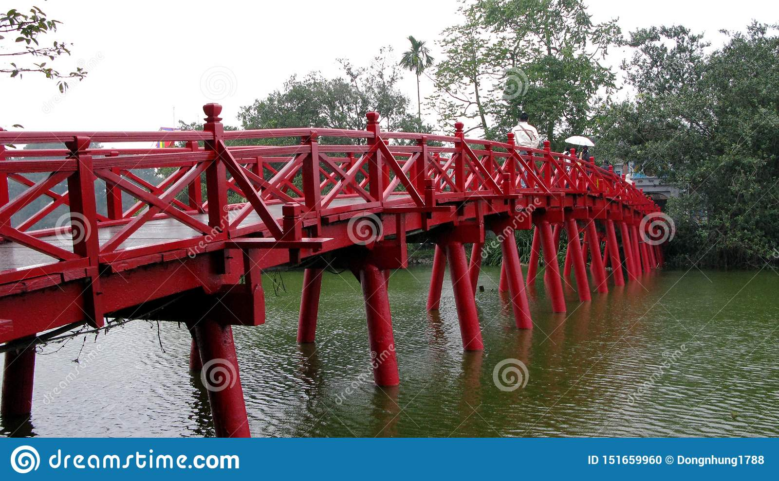 Red wooden bridge by the blue lake