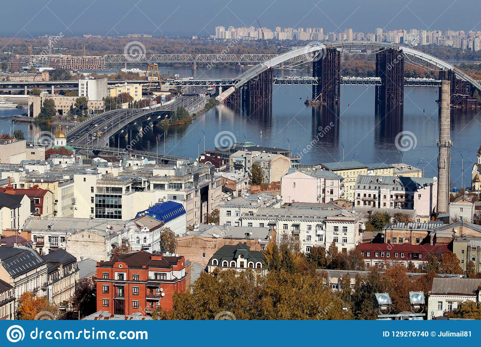 The bridge, which is being repaired, is on the other side of the city. Trees and architecture.Podol, Kiev. Ukraine.