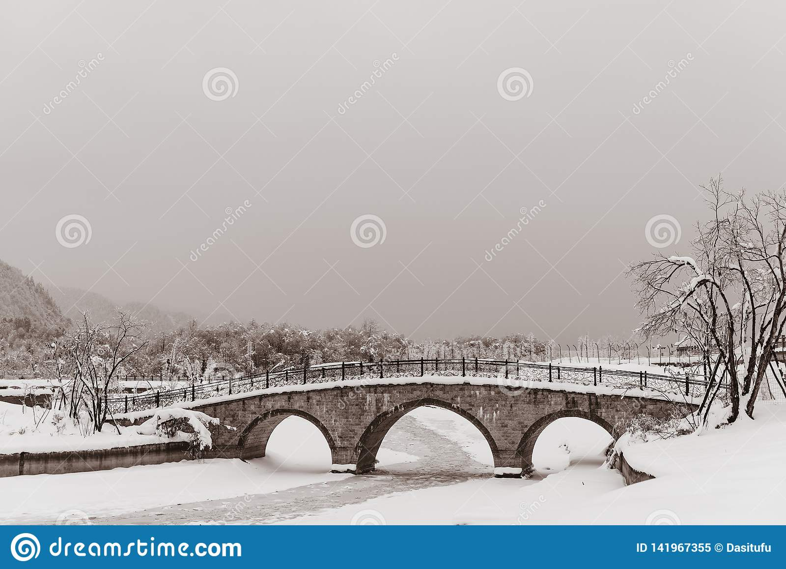 Bridge covered snow with frozen river
