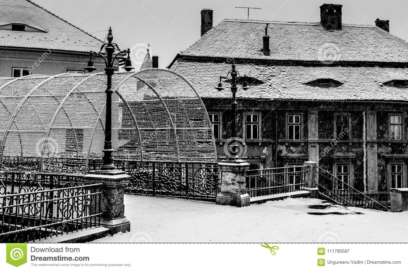The bridge of lies in sibiu and old historic buildings covered in snow in Sibiu, Romania