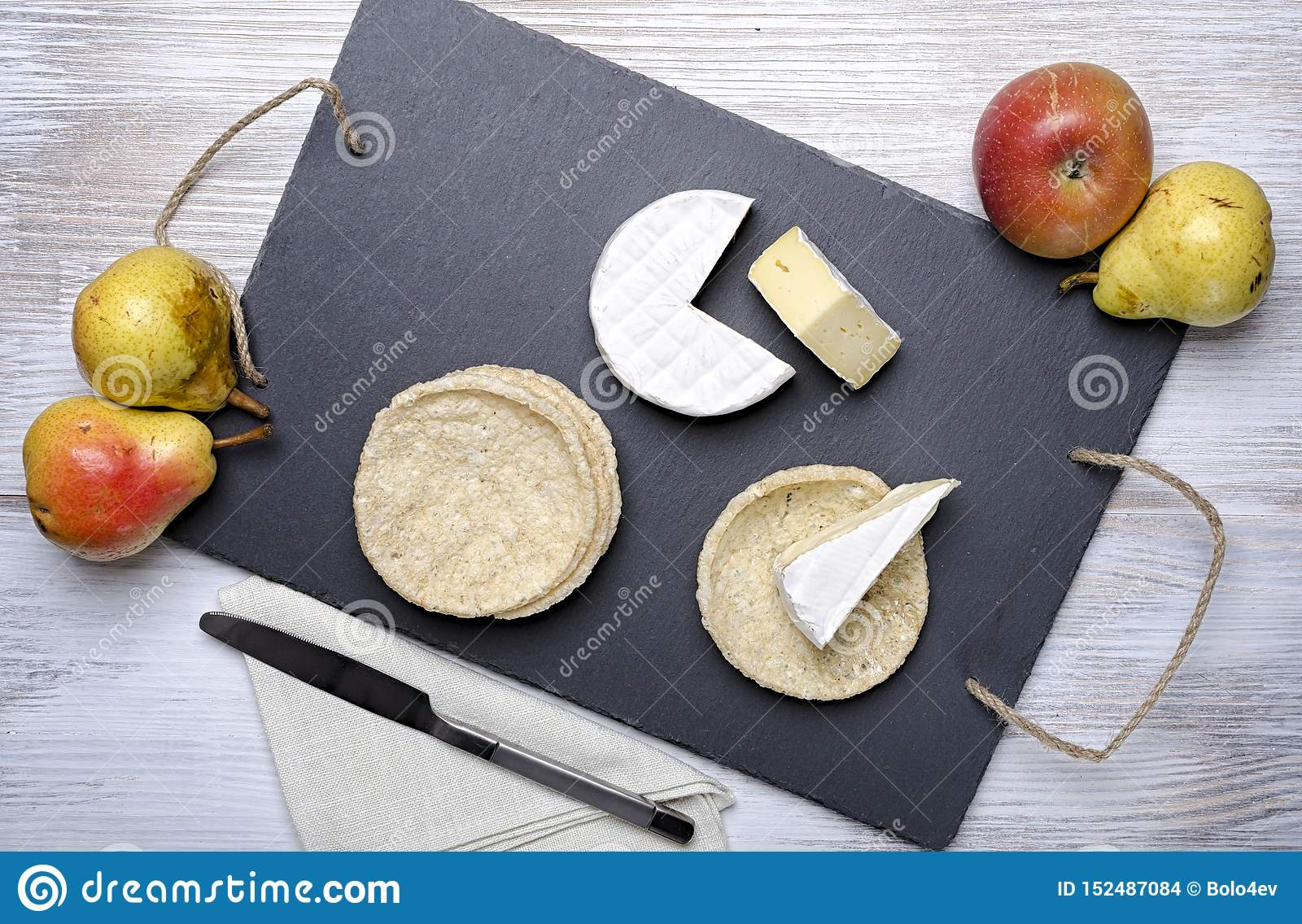 Brie de famille cheese and small round loaves lie on a slate Board on a white wooden background, round cheese, sliced cheese on