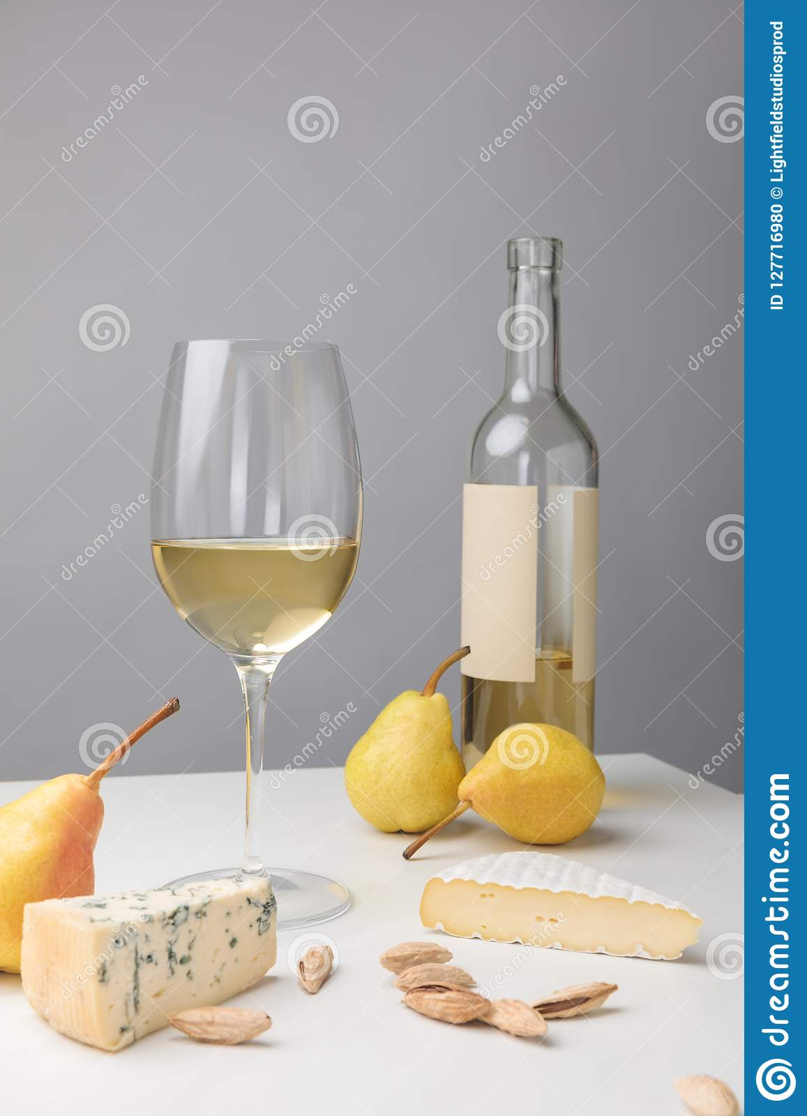 Brie and dorblu cheese with pears, almond, wine glass and bottle on gray