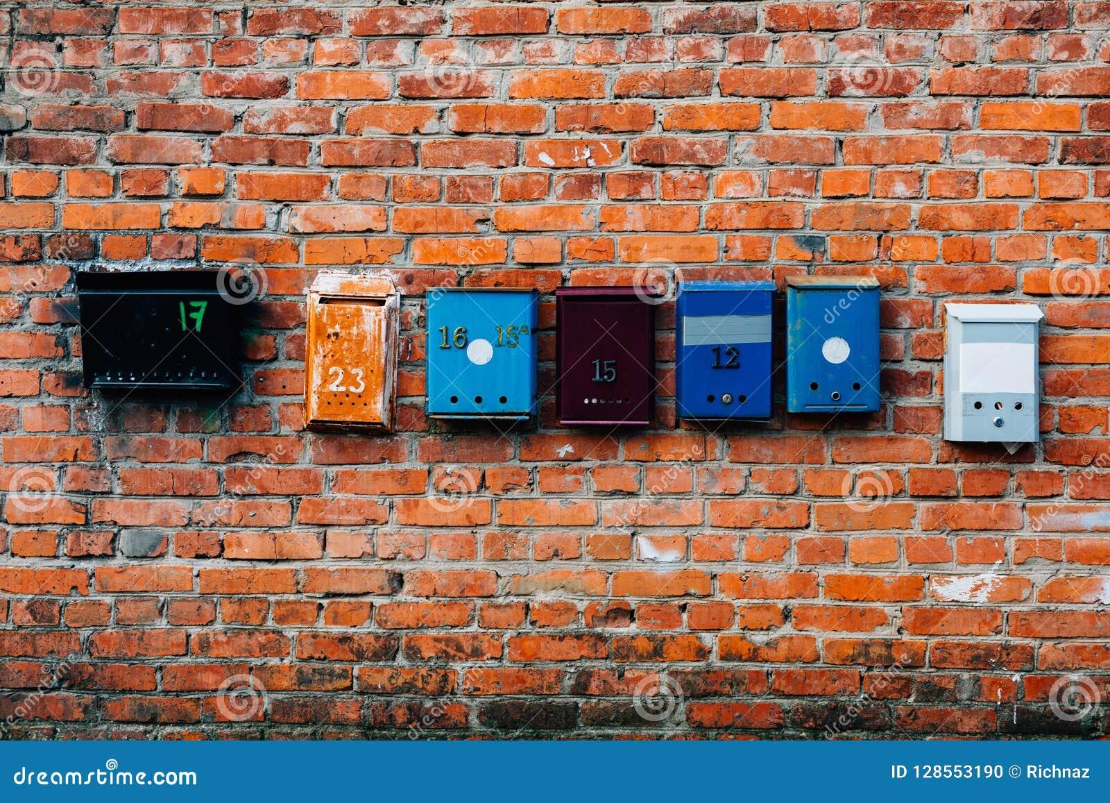 Briefkästen von verschiedenen Farben auf einer Backsteinmauer