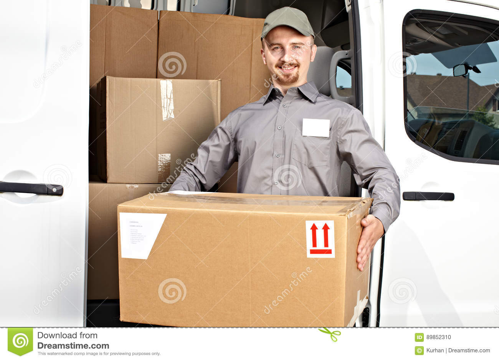 Briefträger mit Paket nahe Lieferwagen