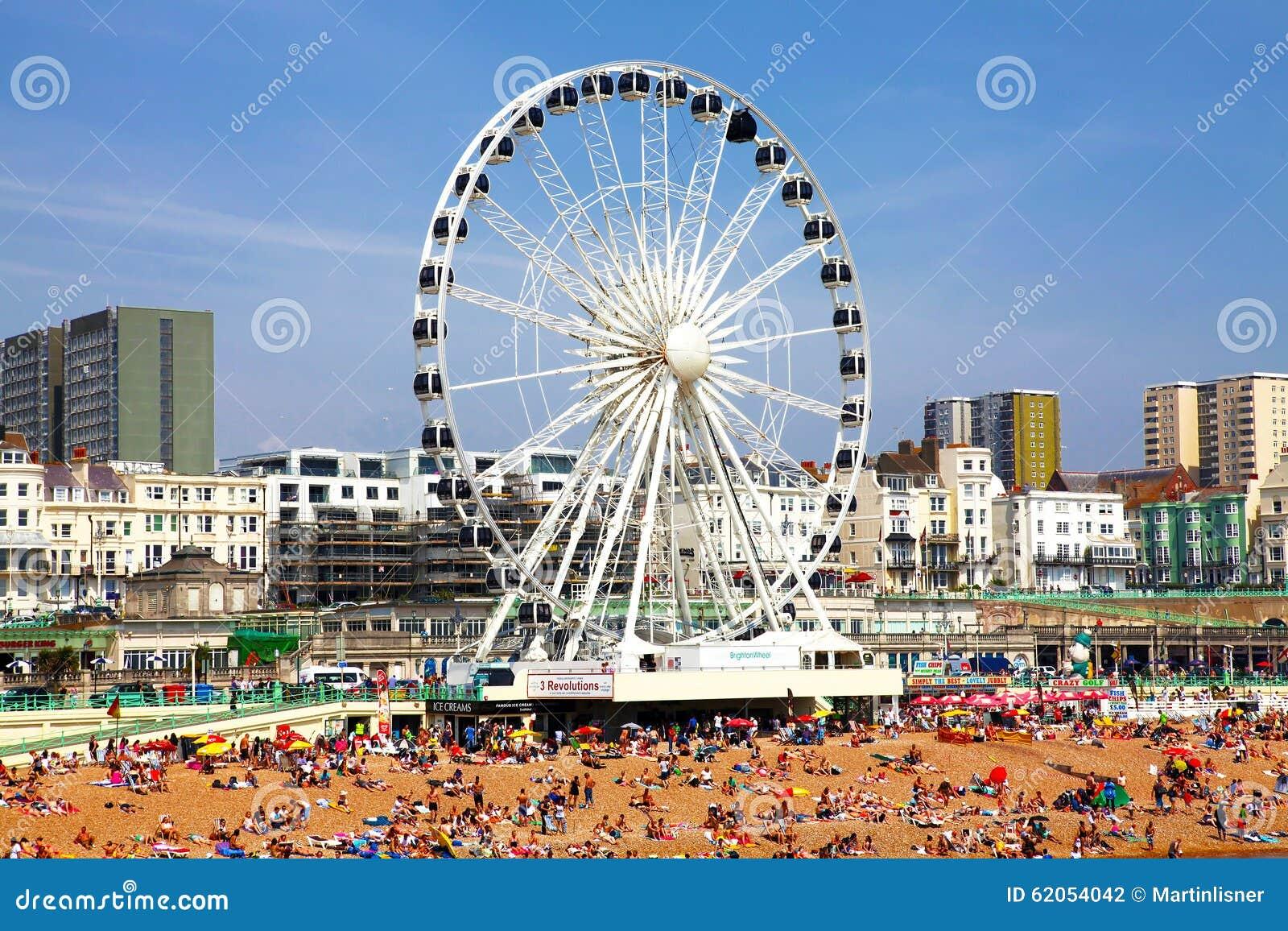 BRIGGHTON - 14 de julho - veja a areia dourada de Brigghton beira-mar à roda e ao parque de diversões de ferris com os grupos de