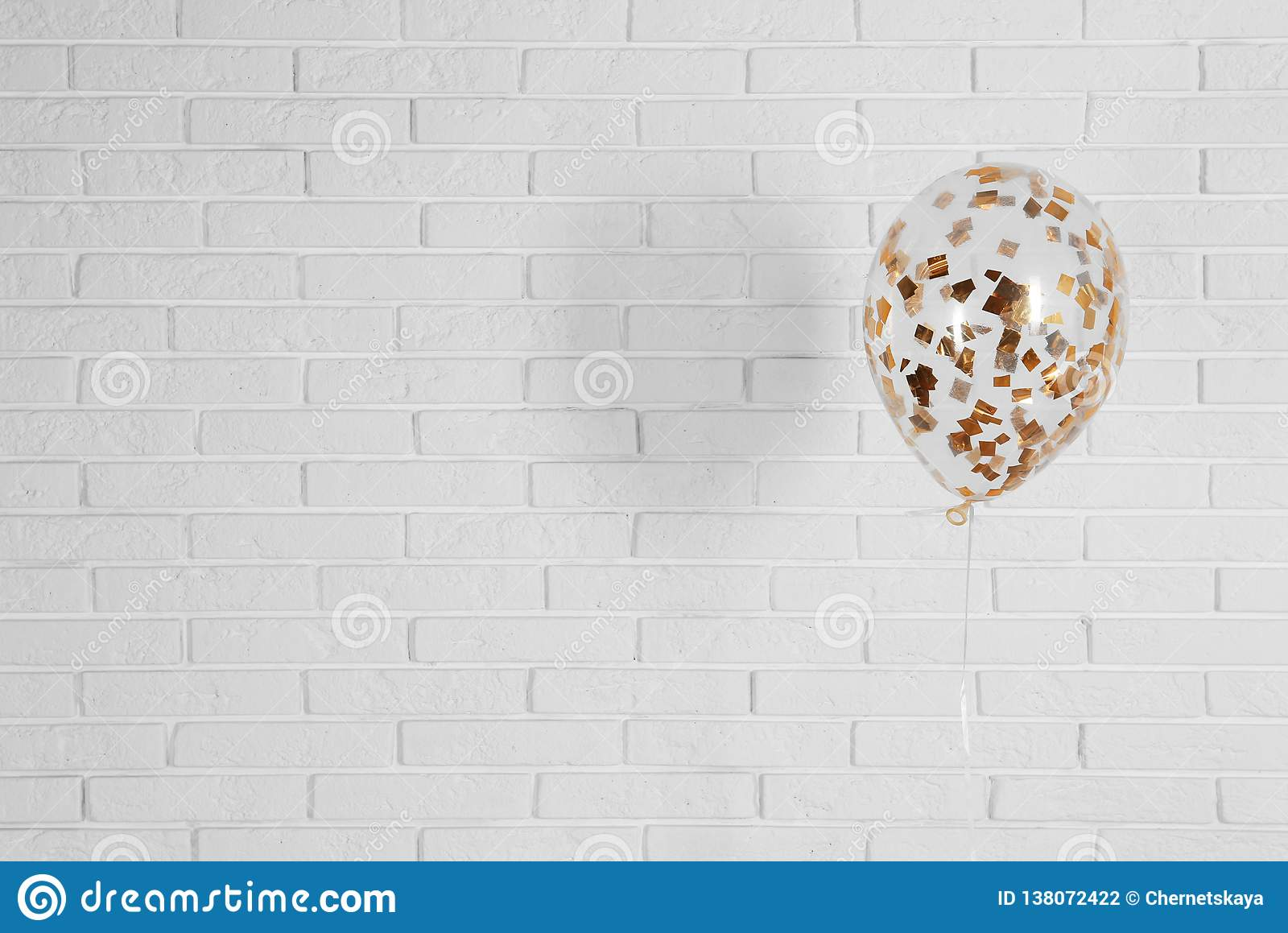 Bright balloon near brick wall, space for text.