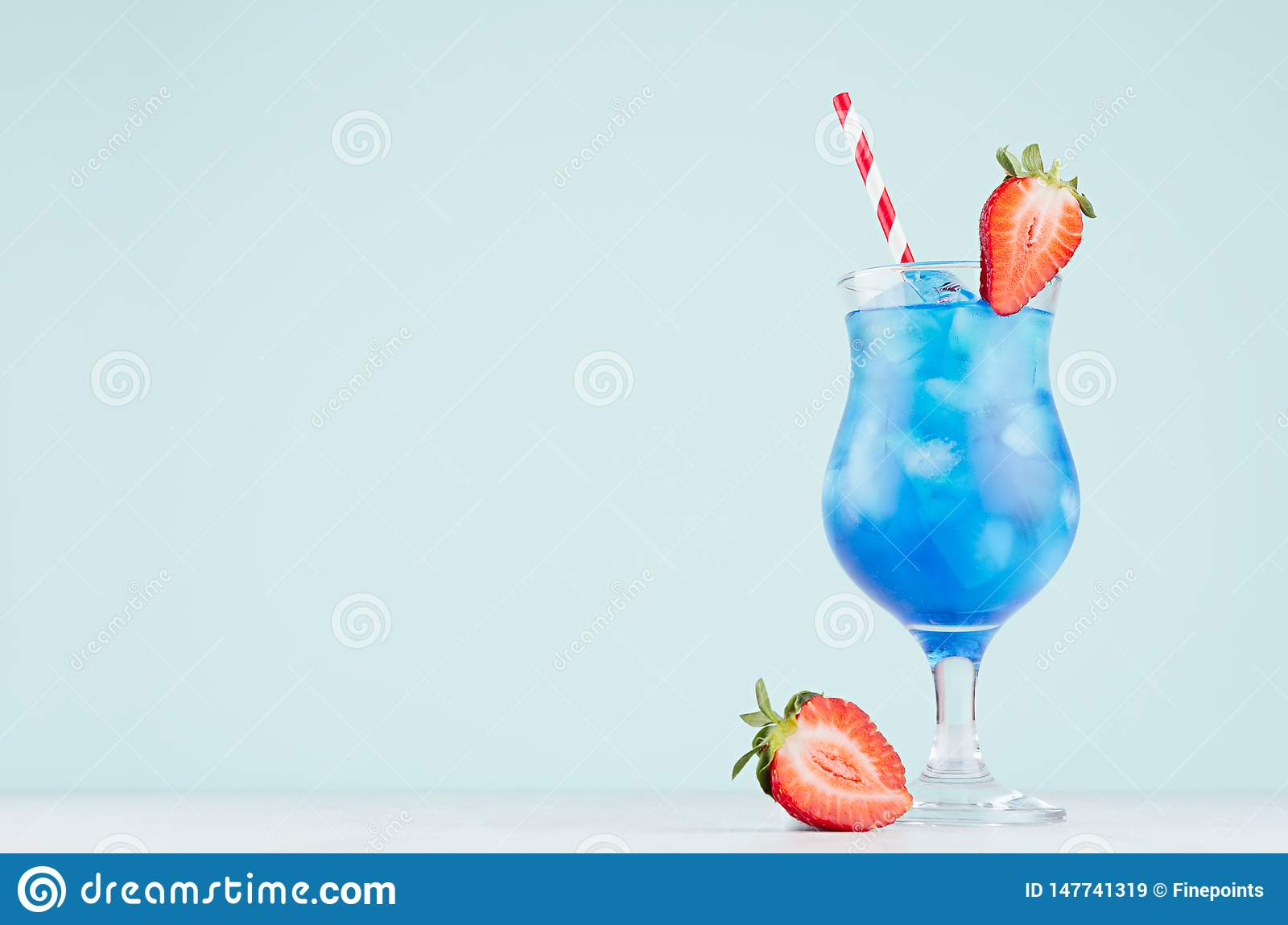 Bright blue tropical cocktail with curacao liquor, ice cubes, strawberry, straw in misted wineglass on soft light blue background.