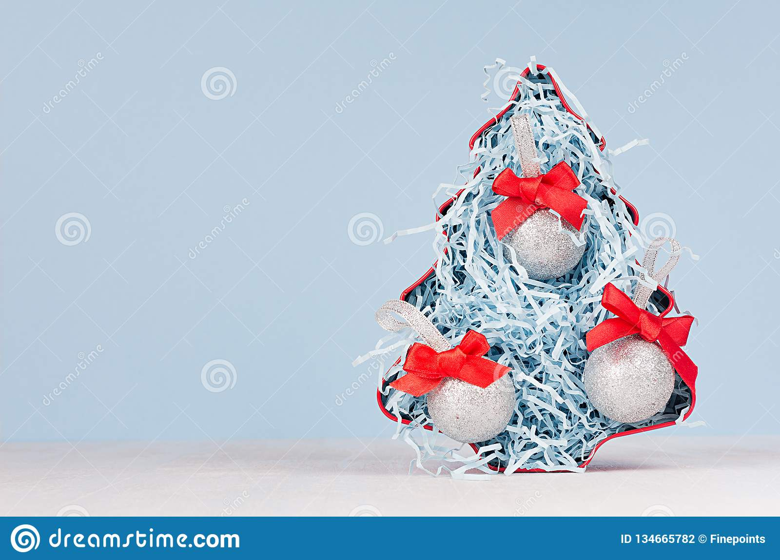 Bright christmas tree in blue and red color with silver glittering balls on white wood board and blue pastel wall, copy space.