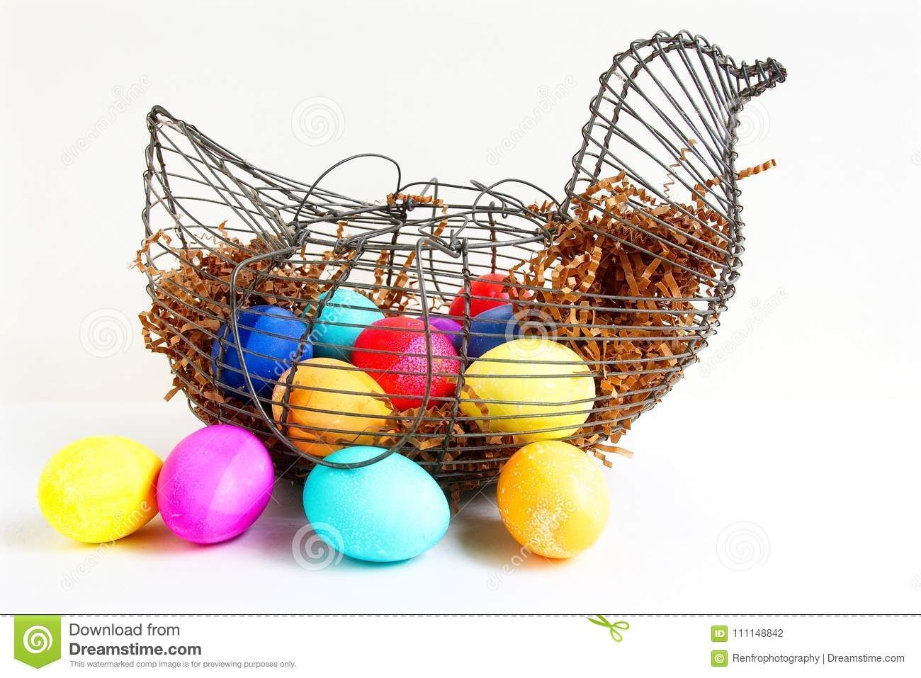 Bright colored Easter eggs in a wire chicken basket.