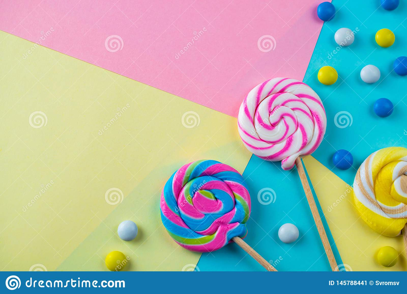 Bright colorful sweet lollipops and candies background flat lay