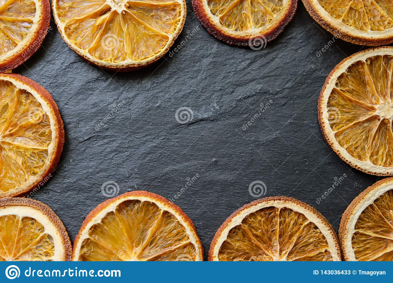 Bright dried orange slices on a stone textured background, copy space, flat lay, top view