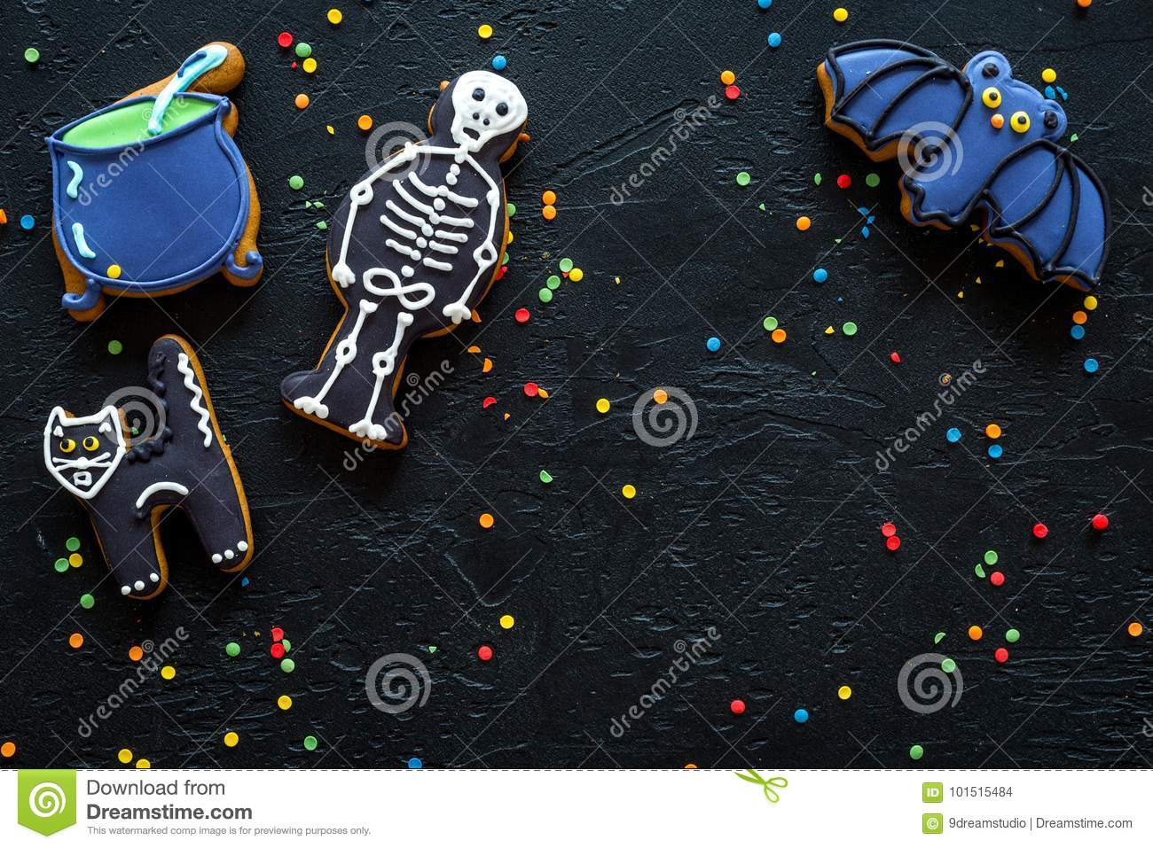 Halloween gingerbread cookies with pictures of bat, skeleton on black background top view copyspace