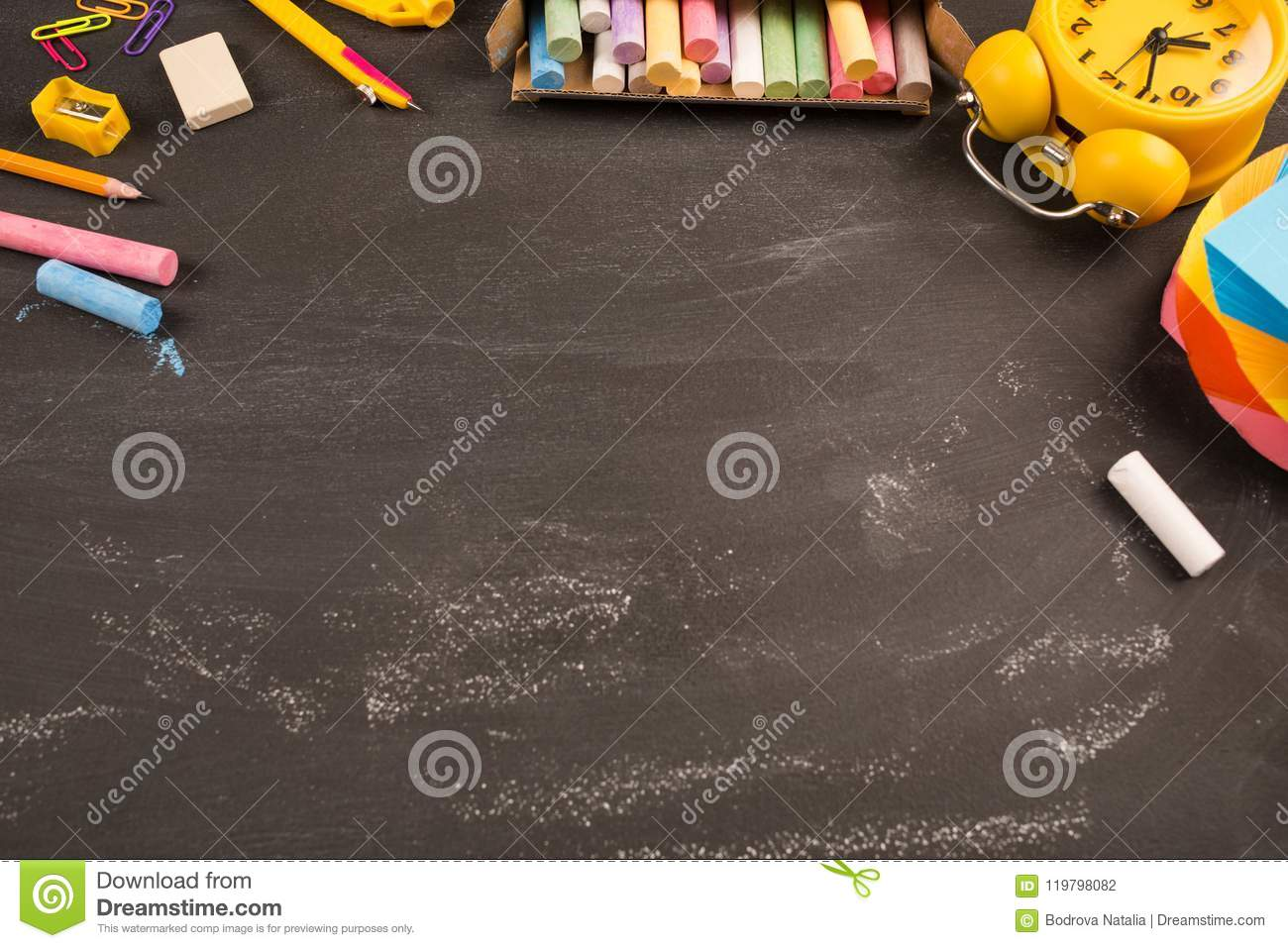 Bright office supplies, yellow alarm clock on black chalkboard top view, copy space. concept: back to school