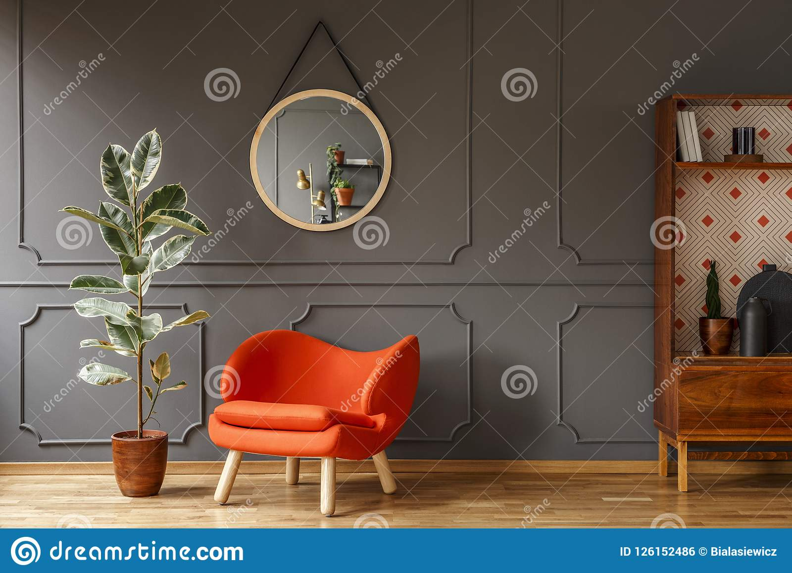 Bright orange armchair, a retro wooden cabinet and a mirror on a