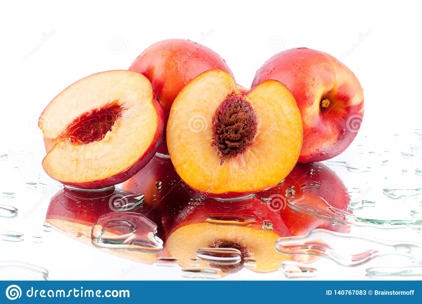 Peach whole and cutted into two halves in water drops on white background isolated close up