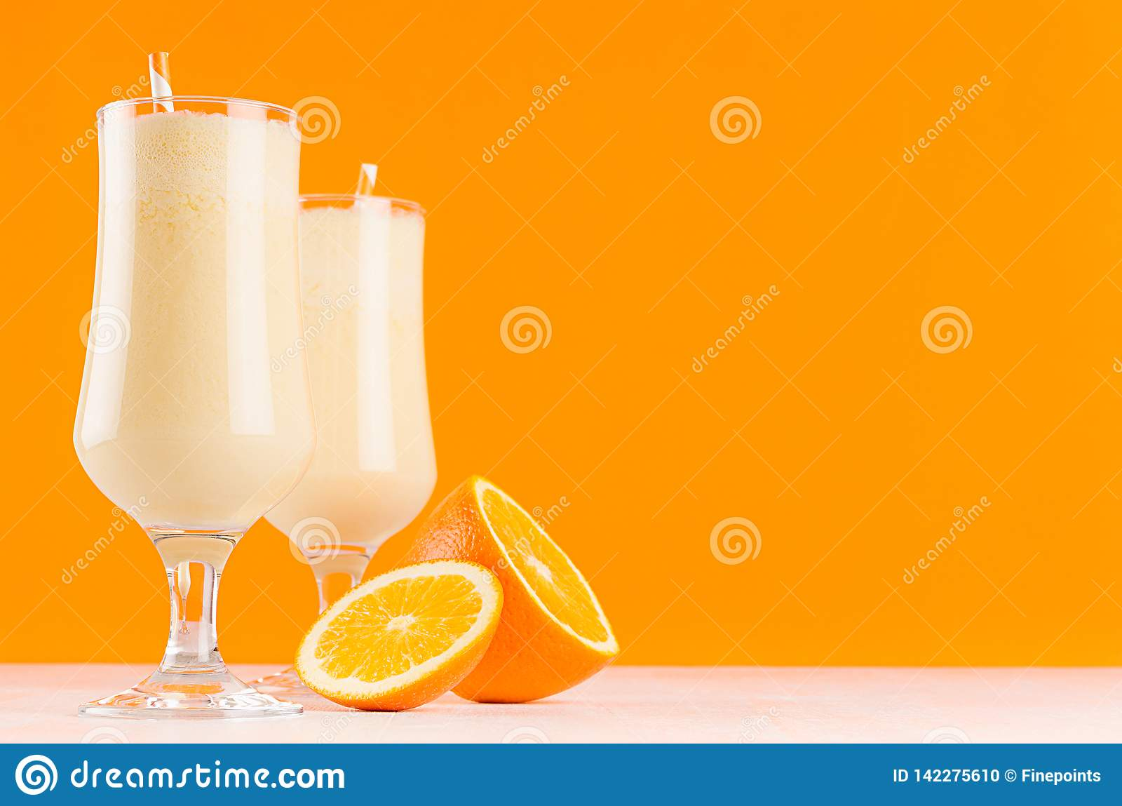 Bright oranges milkshakes with slices citrus, striped straw on white wooden table and colorful orange wall.