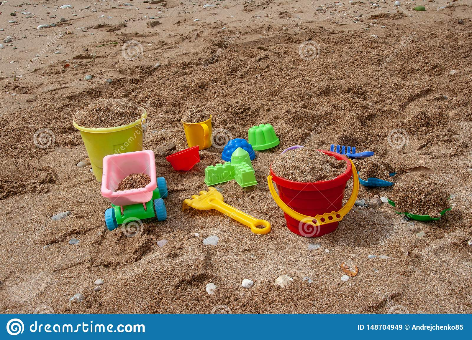 Bright plastic children`s toys in the sand. Concept of beach recreation for children.