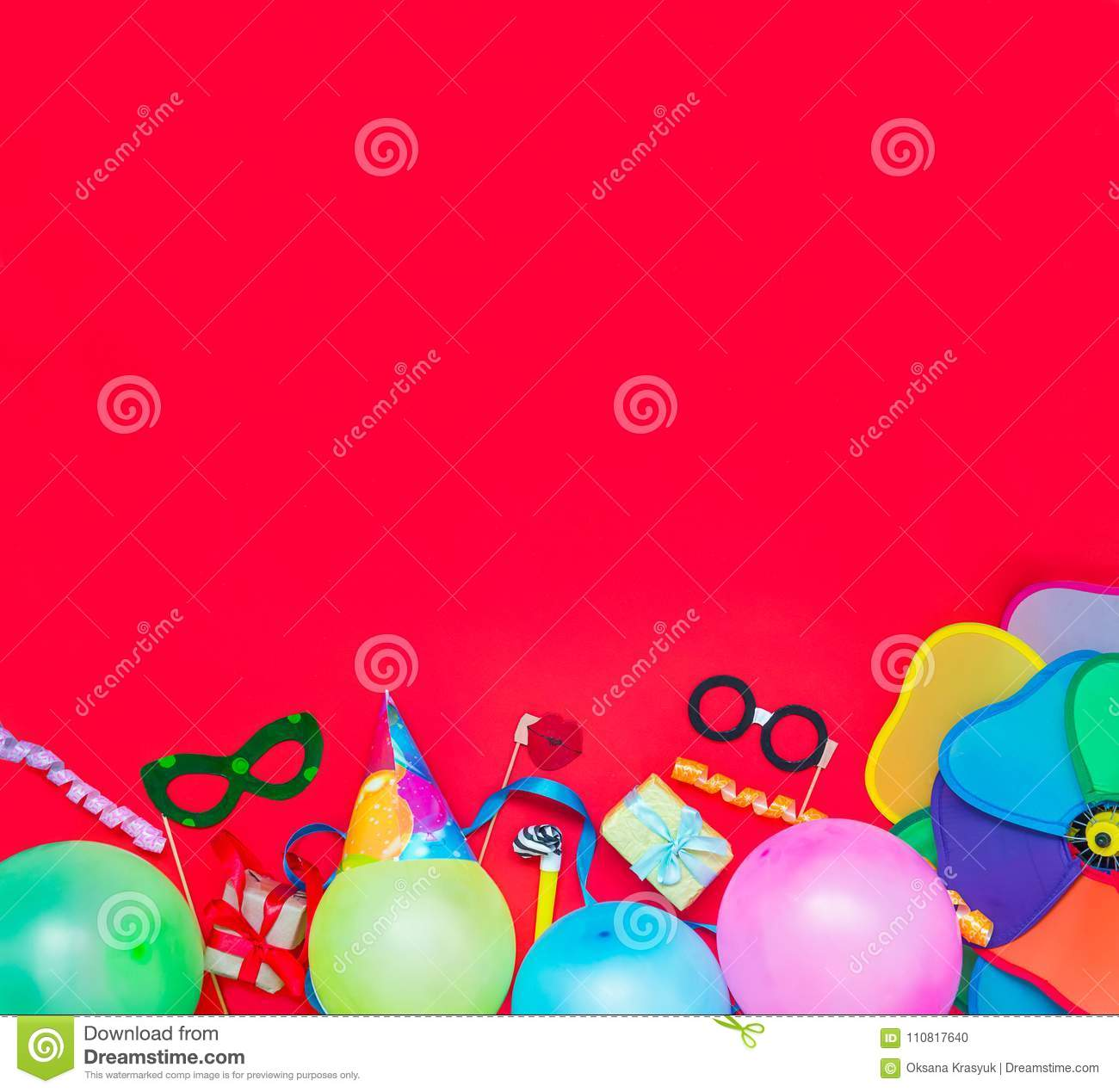 Bright red Festive background with party tools and decoration - baloons, funny carnival masks, festive tinsel. Happy birthday gree