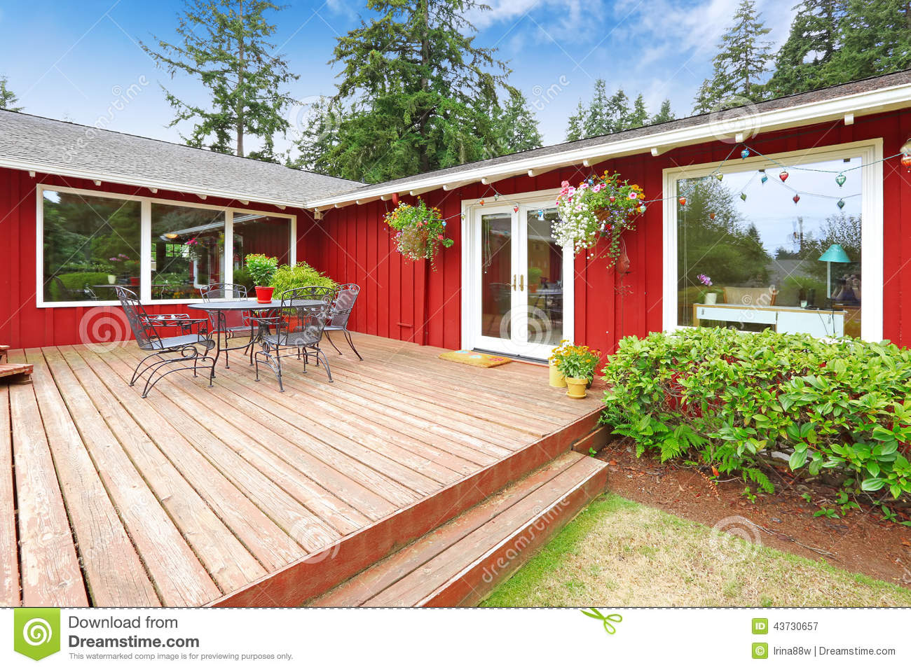 Bright Red House With Walkout Deck And Patio Area Stock