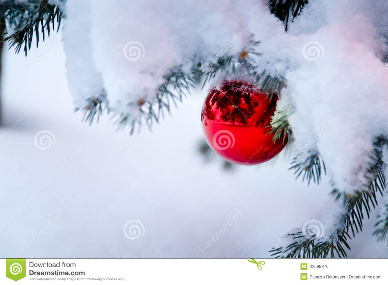 Bright Red Ornament Hanging From A Snow Covered Ch Stock