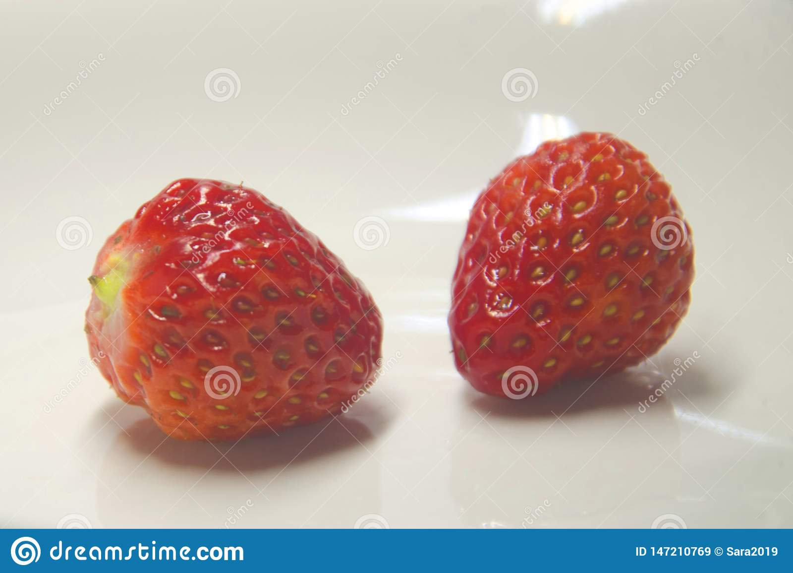 Bright red strawberry against white background