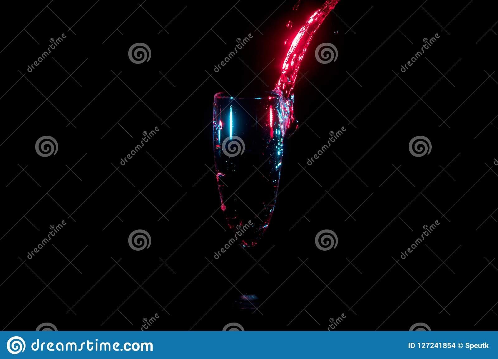 Bright red water stream pouring into a glass isolated on a black background
