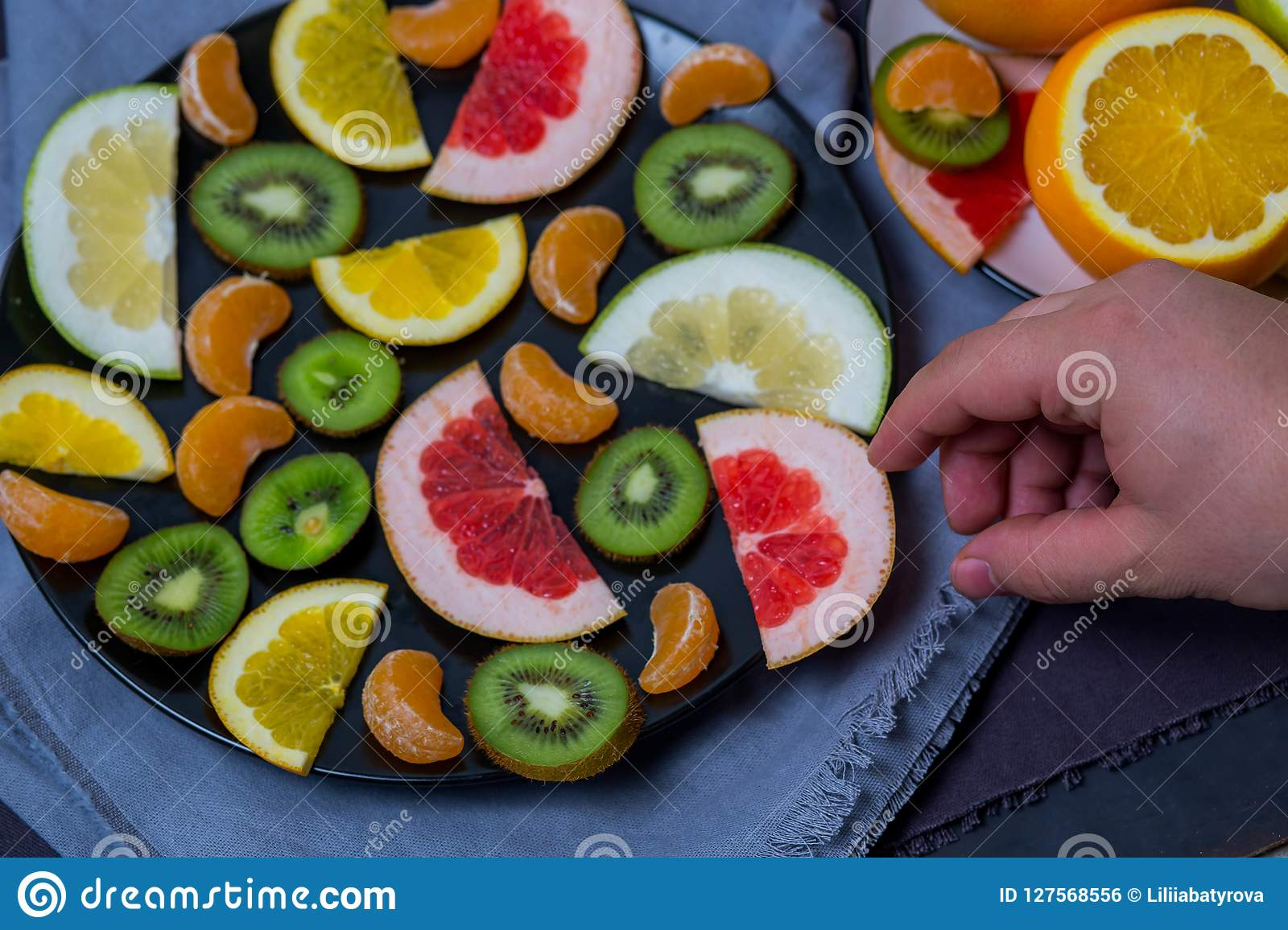 Bright ripe delicious fruits citrus oranges cut in a large black plate on a blue fabric background kitchen towels men`s hand