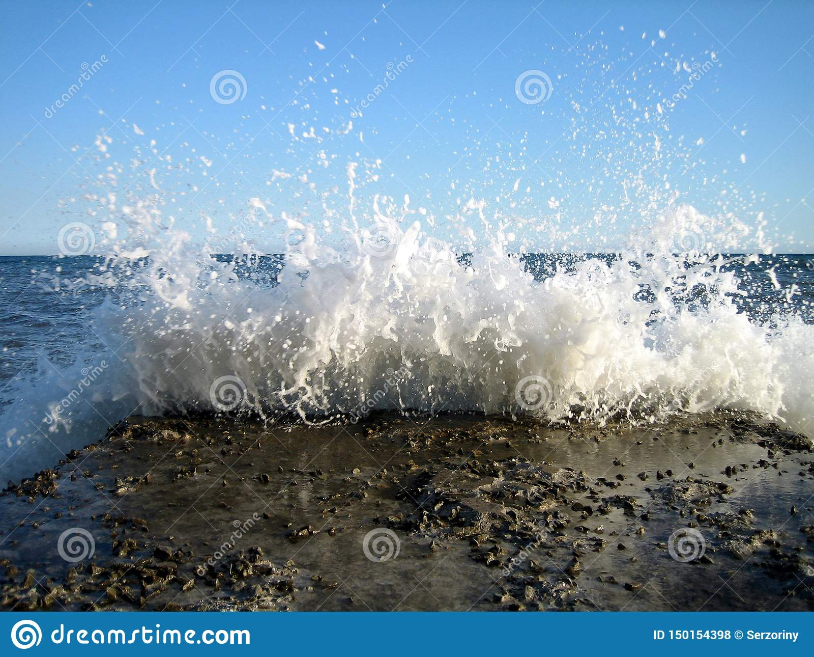 Bright splashes of sea waves on old stone pier on a Sunny day