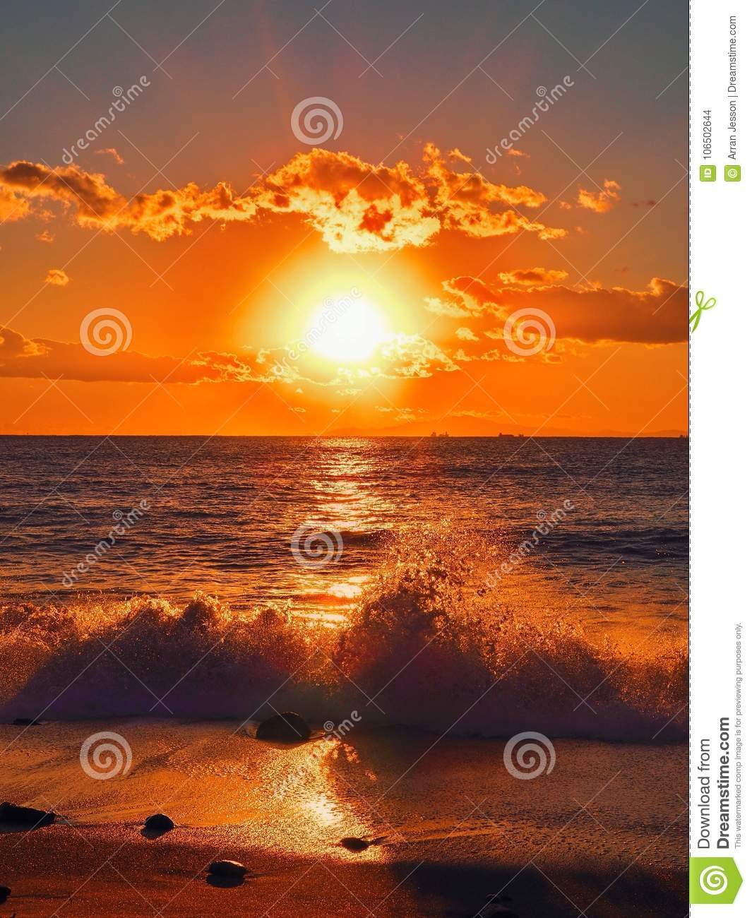 Wave breaks in front of beach sunset