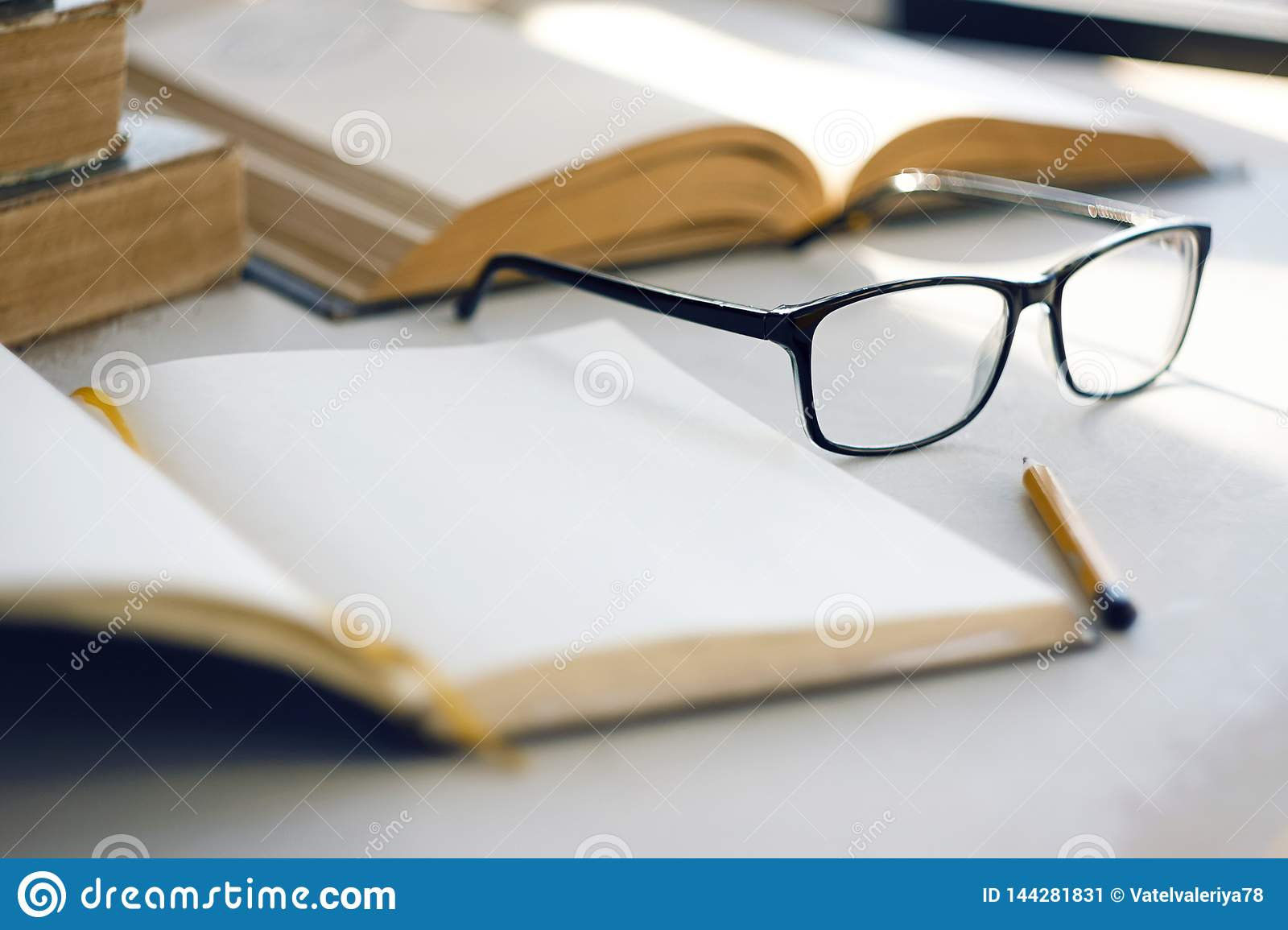 The bright sun illuminates old encyclopedias, an notebook, a simple pencil and glasses