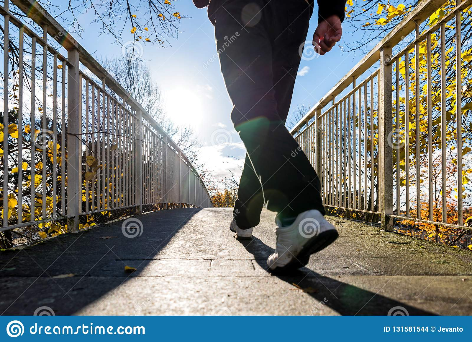 Bright sunny morning view of man walking on pedestrian bridge in british autumn