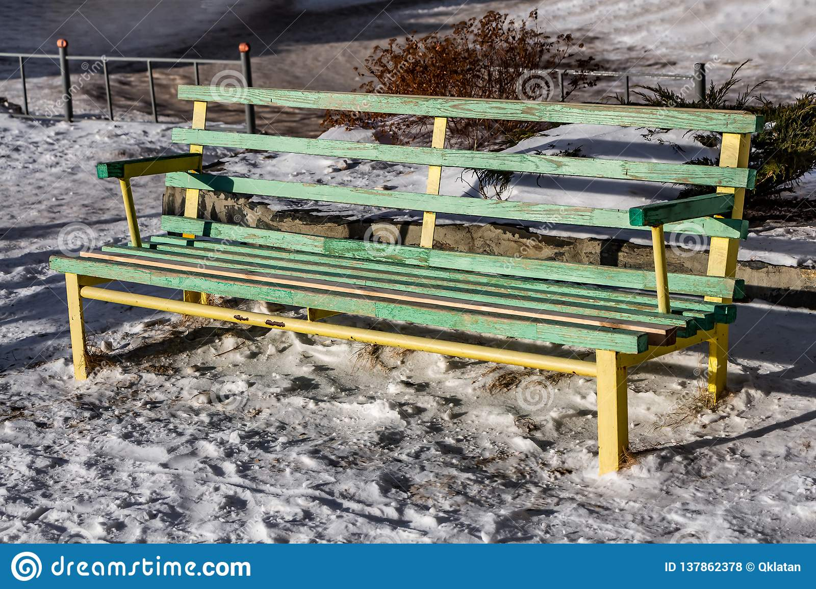 A bright wet wooden painted yellow and green color beautiful bench with yellow metal legs is on a white snow in the courtyard in