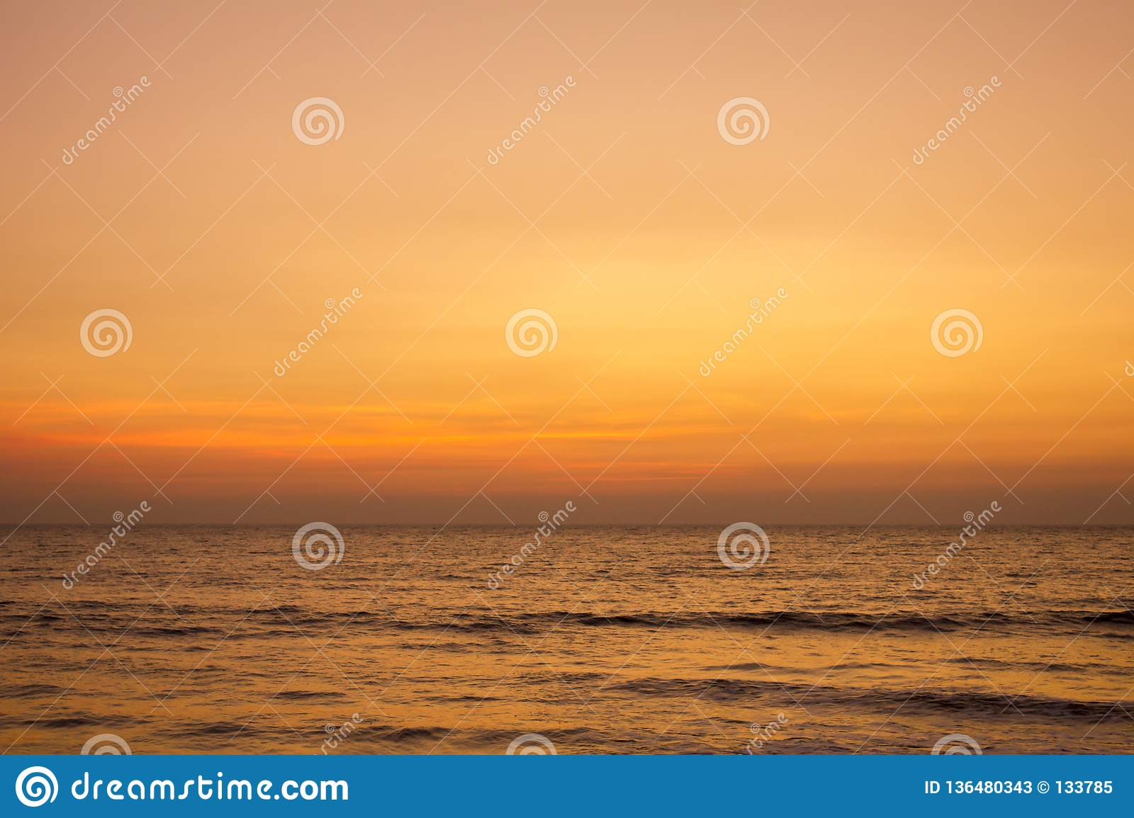 A bright yellow gray pink sunset sky over the ocean