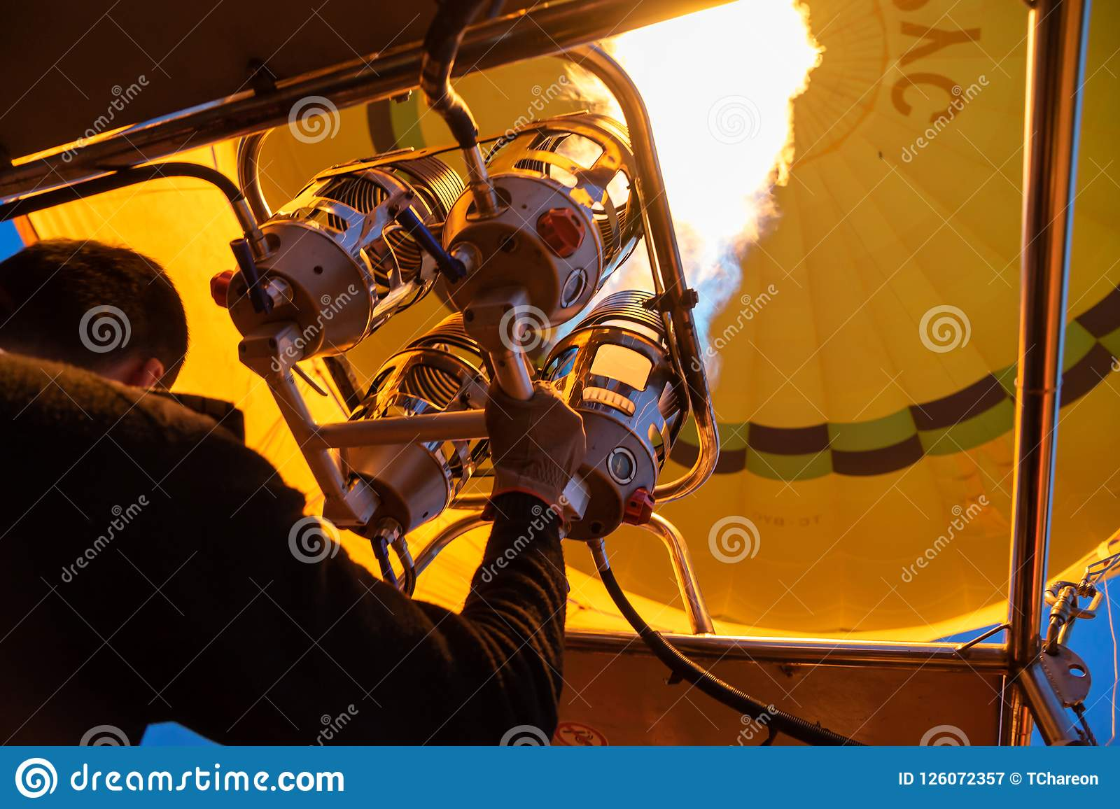 Bright yellow hot air balloon flying with gas fire flame heat equipment by pilot over Cappadocia, low angle view from inside